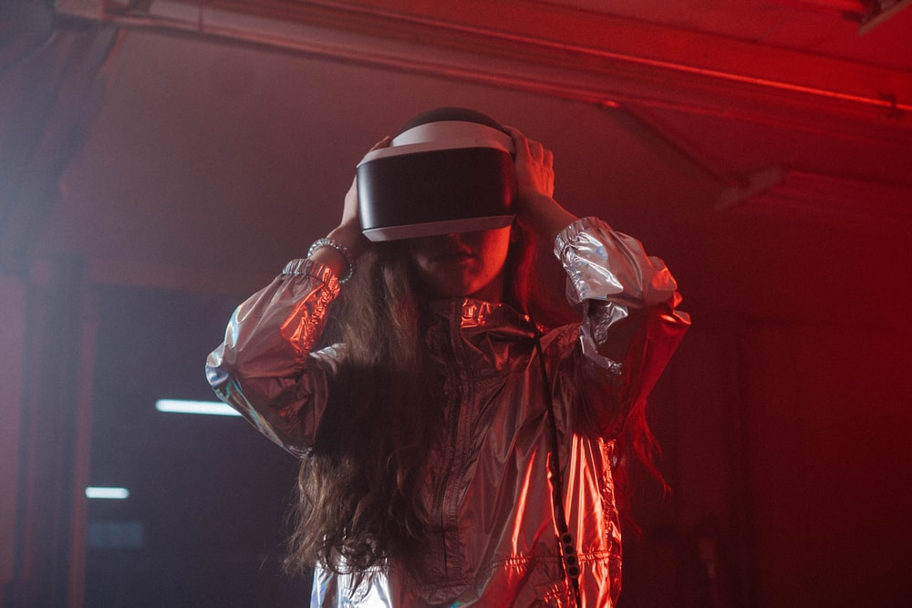 woman in white long sleeve shirt wearing black and white vr goggles