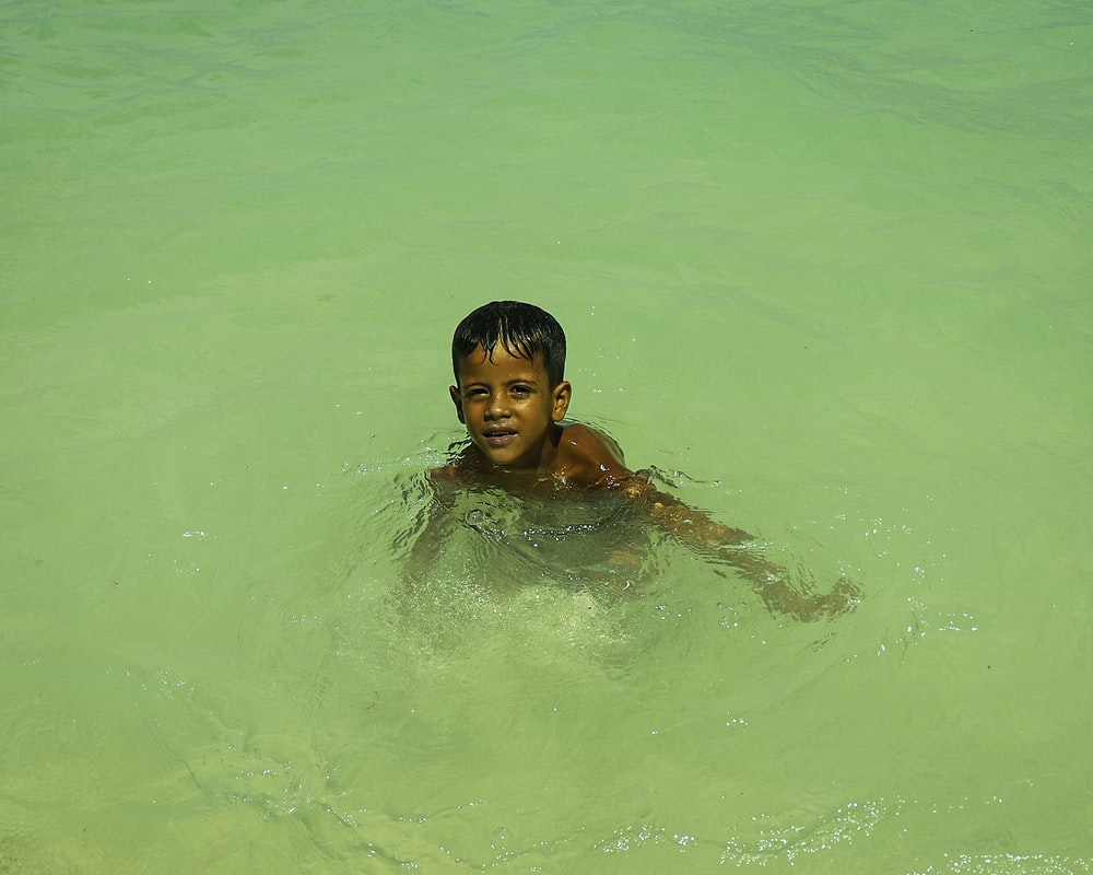 2 boys in water during daytime