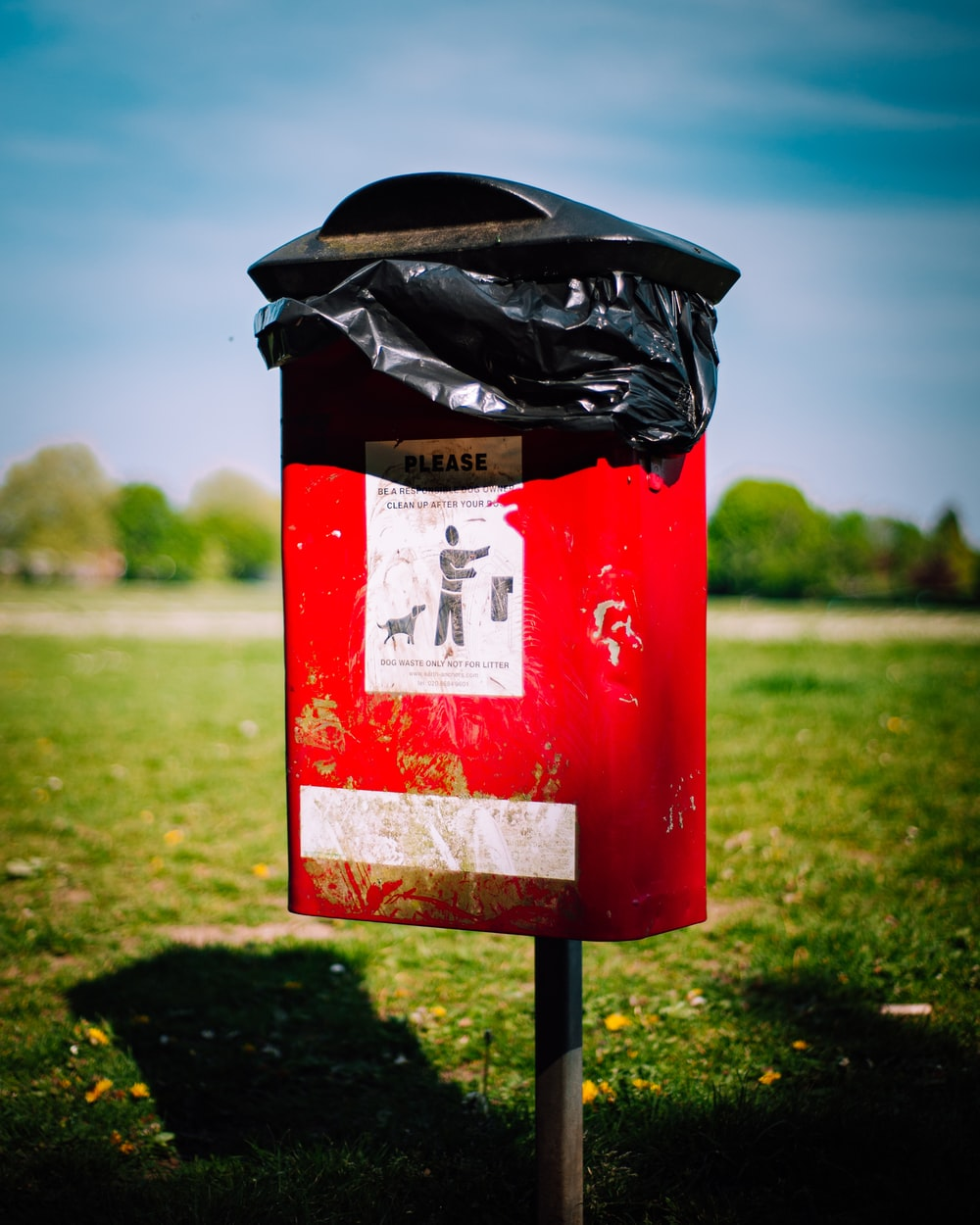 red and black trash bin on green grass field during daytime