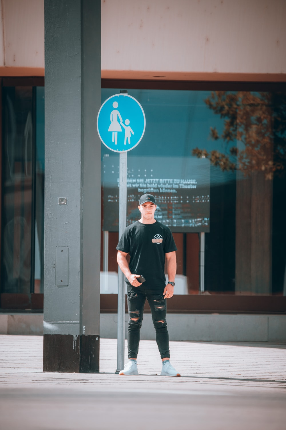 man in black crew neck t-shirt and black pants standing beside glass window