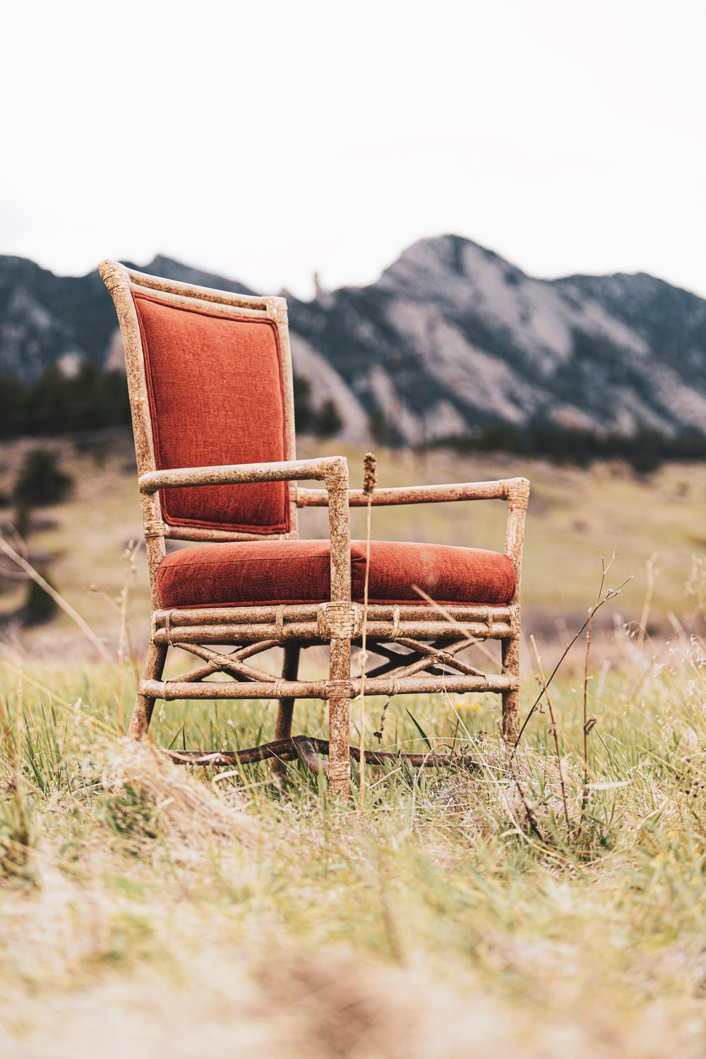 brown wooden armchair on green grass field during daytime