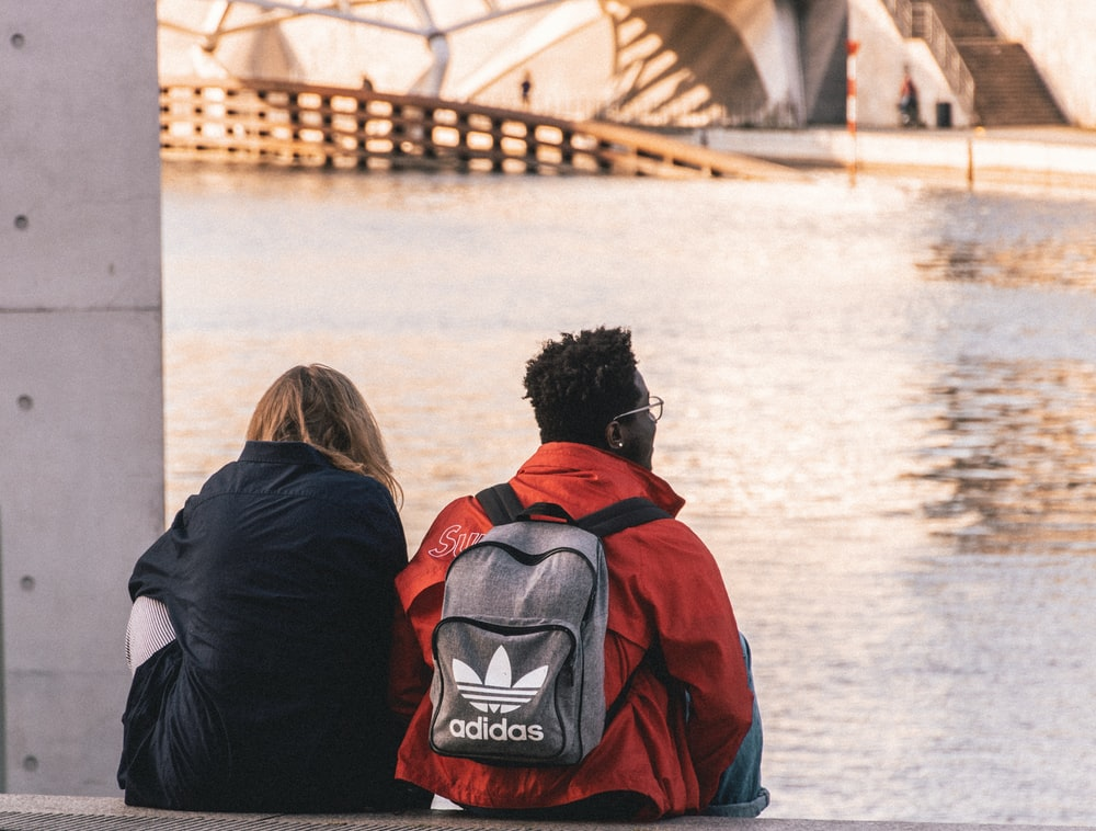 man and woman wearing black and red backpacks