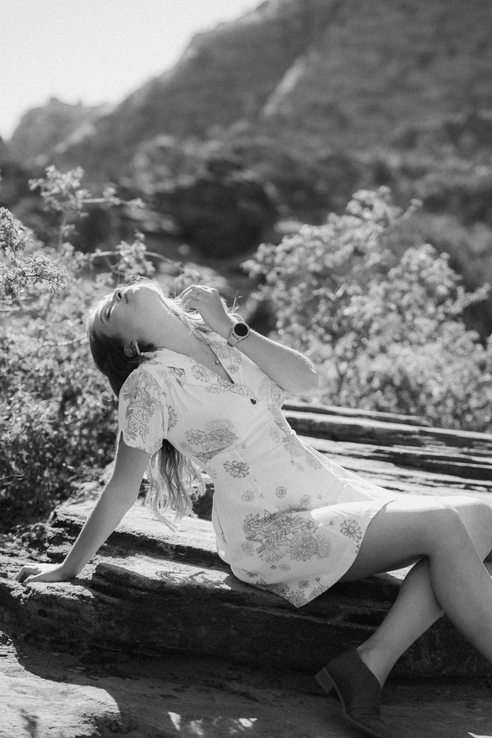 grayscale photo of girl in floral dress sitting on wooden bench
