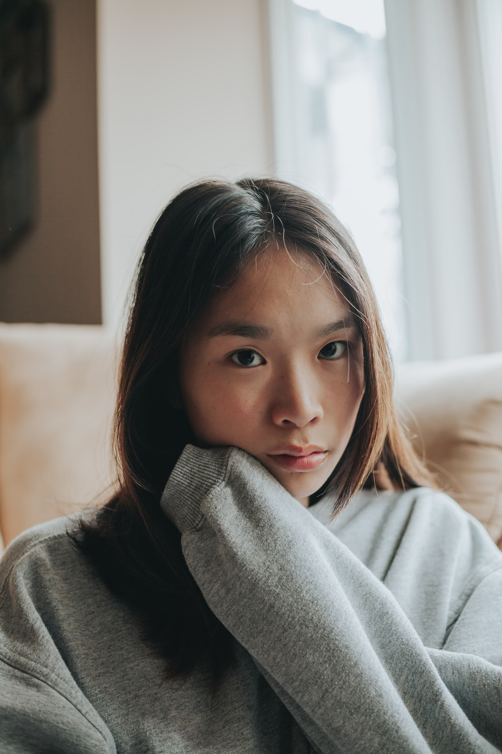 girl in gray sweater sitting on white couch