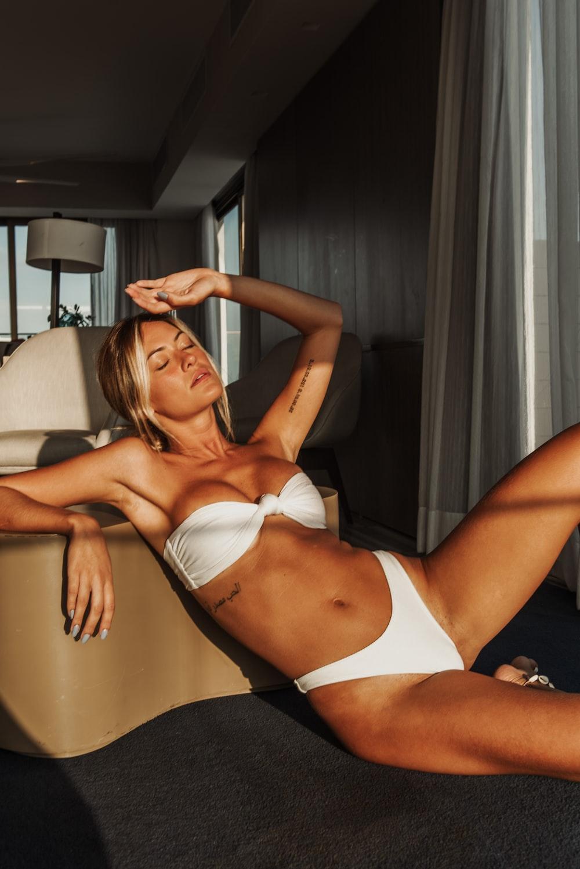 woman in white bikini standing near brown wall