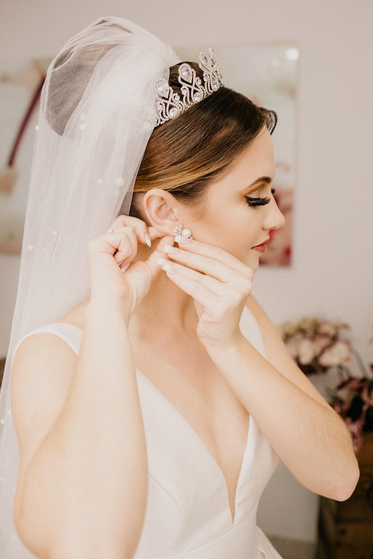 woman in white sleeveless dress wearing silver tiara
