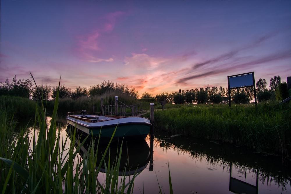 white boat on lake during sunset