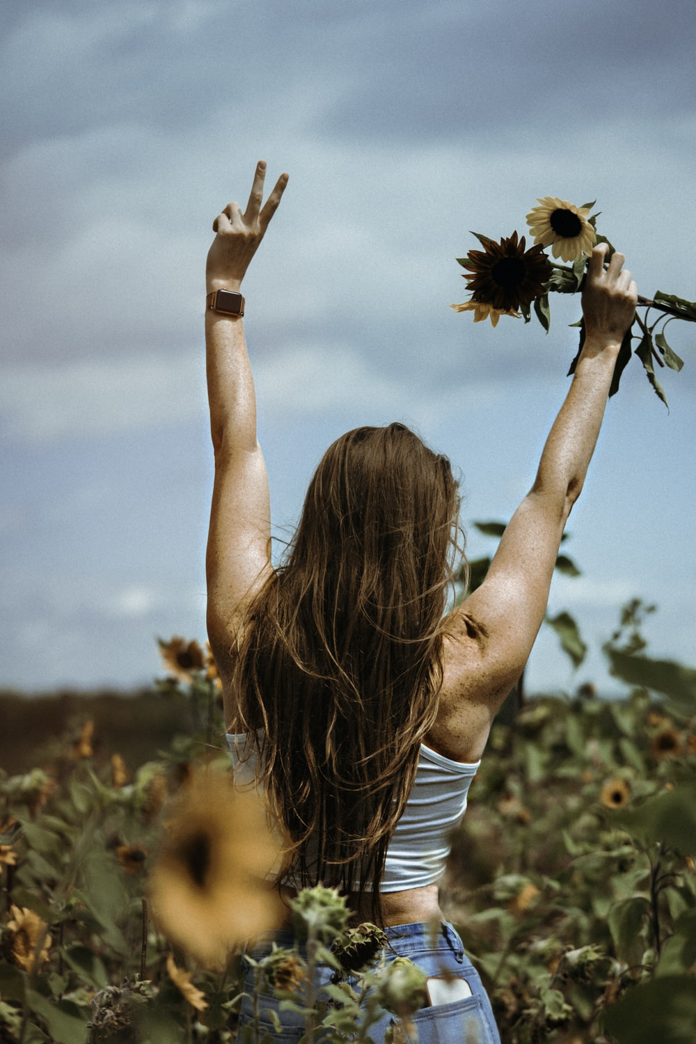 woman in white tank top holding sunflower during daytime