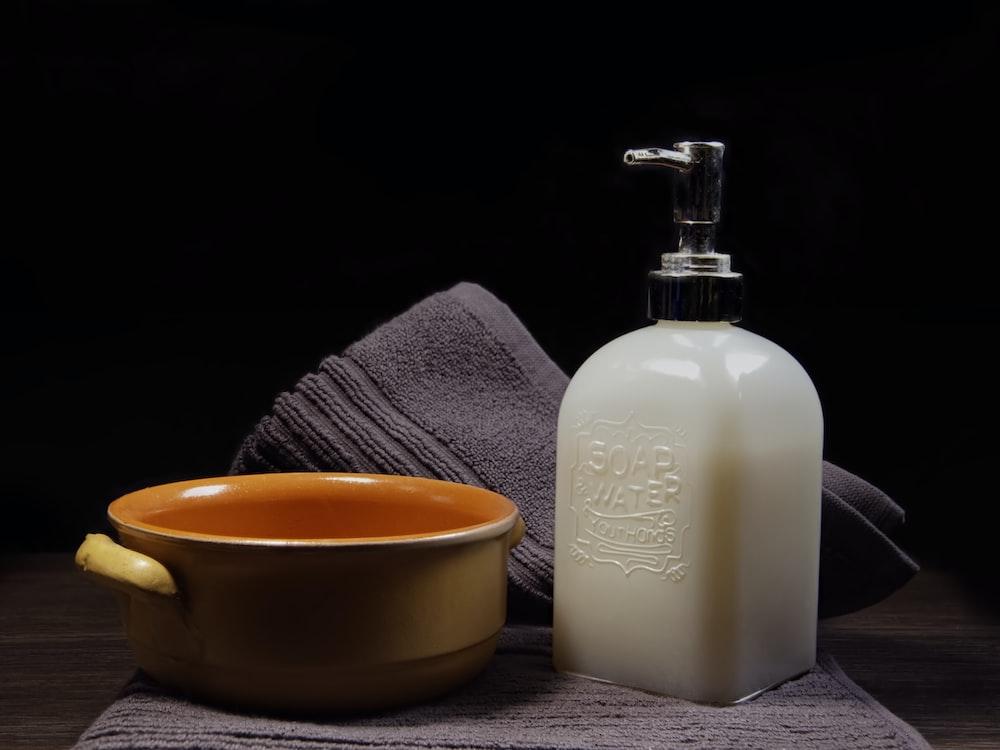 white plastic pump bottle beside yellow ceramic mug