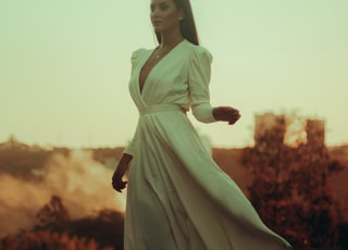 woman in white long sleeve dress standing on red flower field during daytime