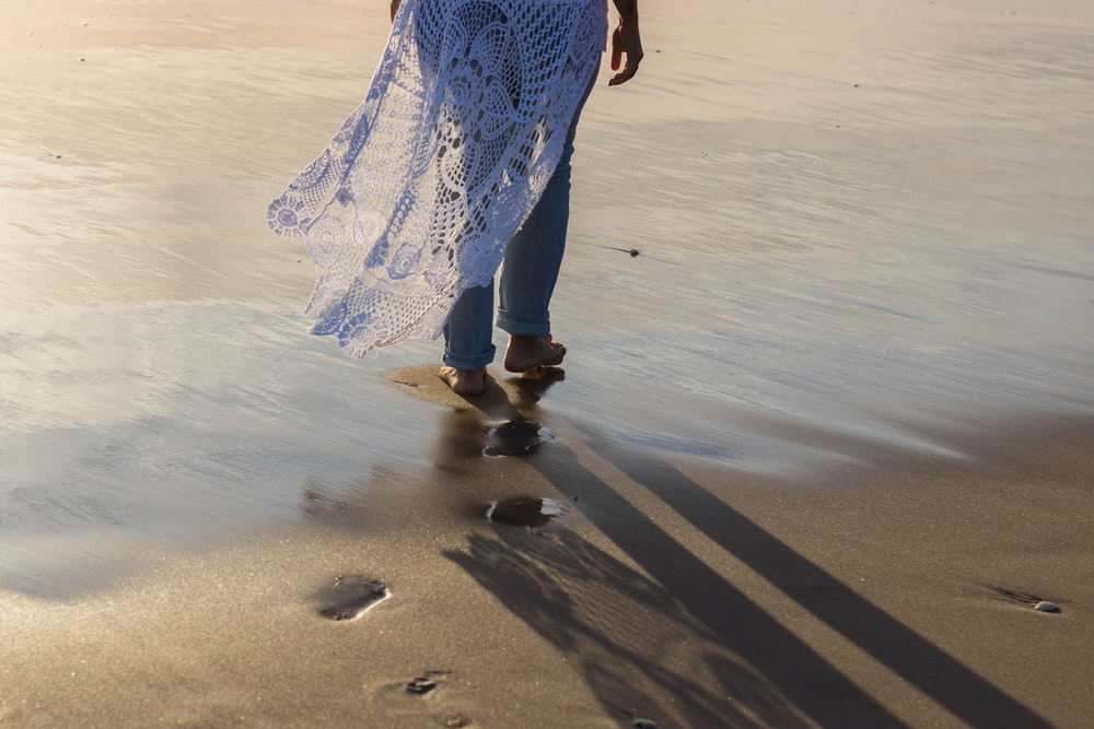 woman in blue and white dress walking on beach during daytime