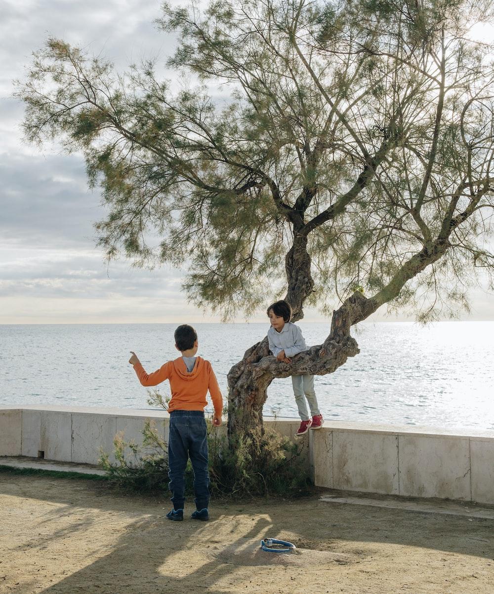 man in orange shirt standing near body of water during daytime