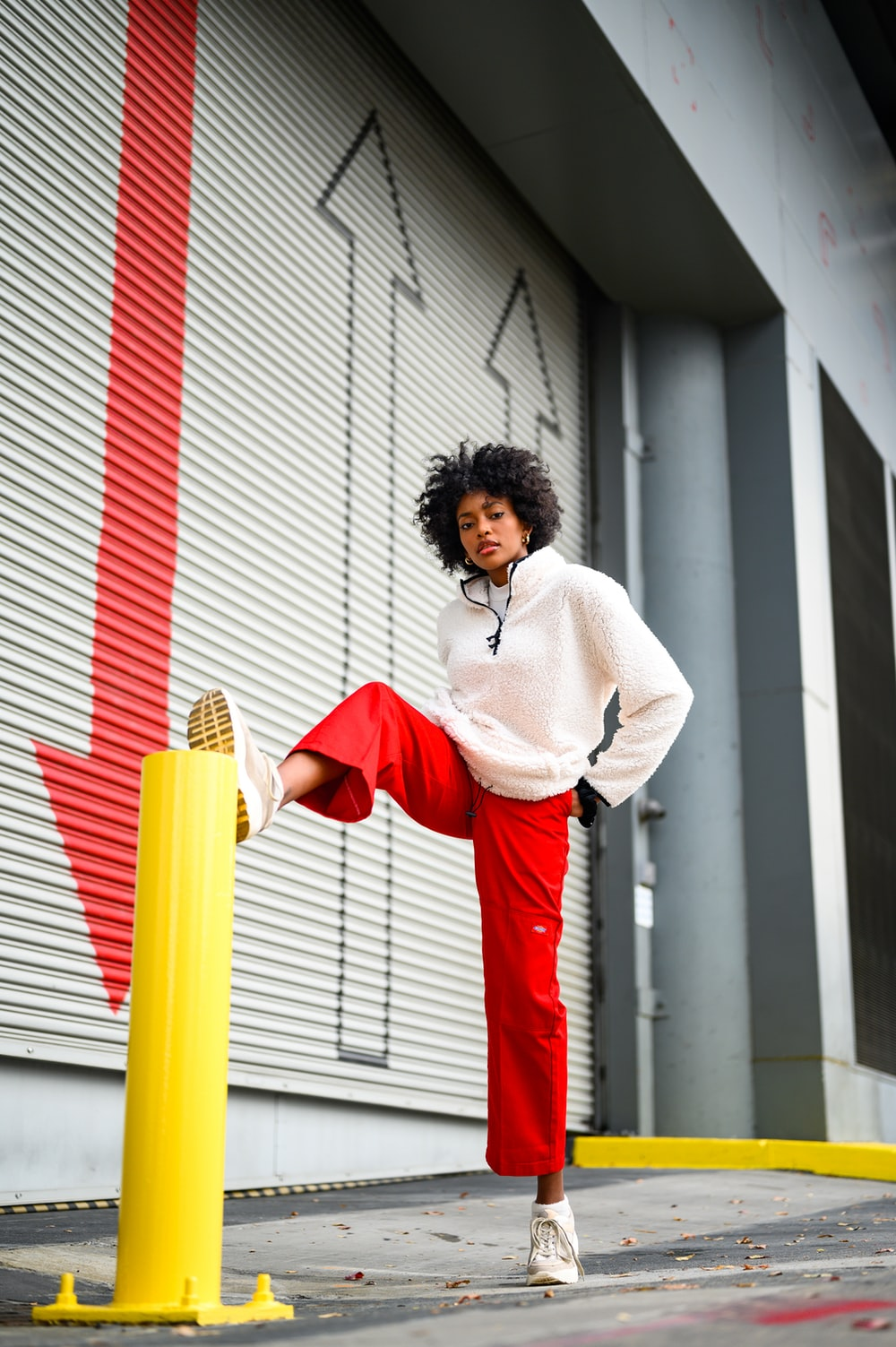 woman in white long sleeve shirt and red skirt standing beside white and red striped wall