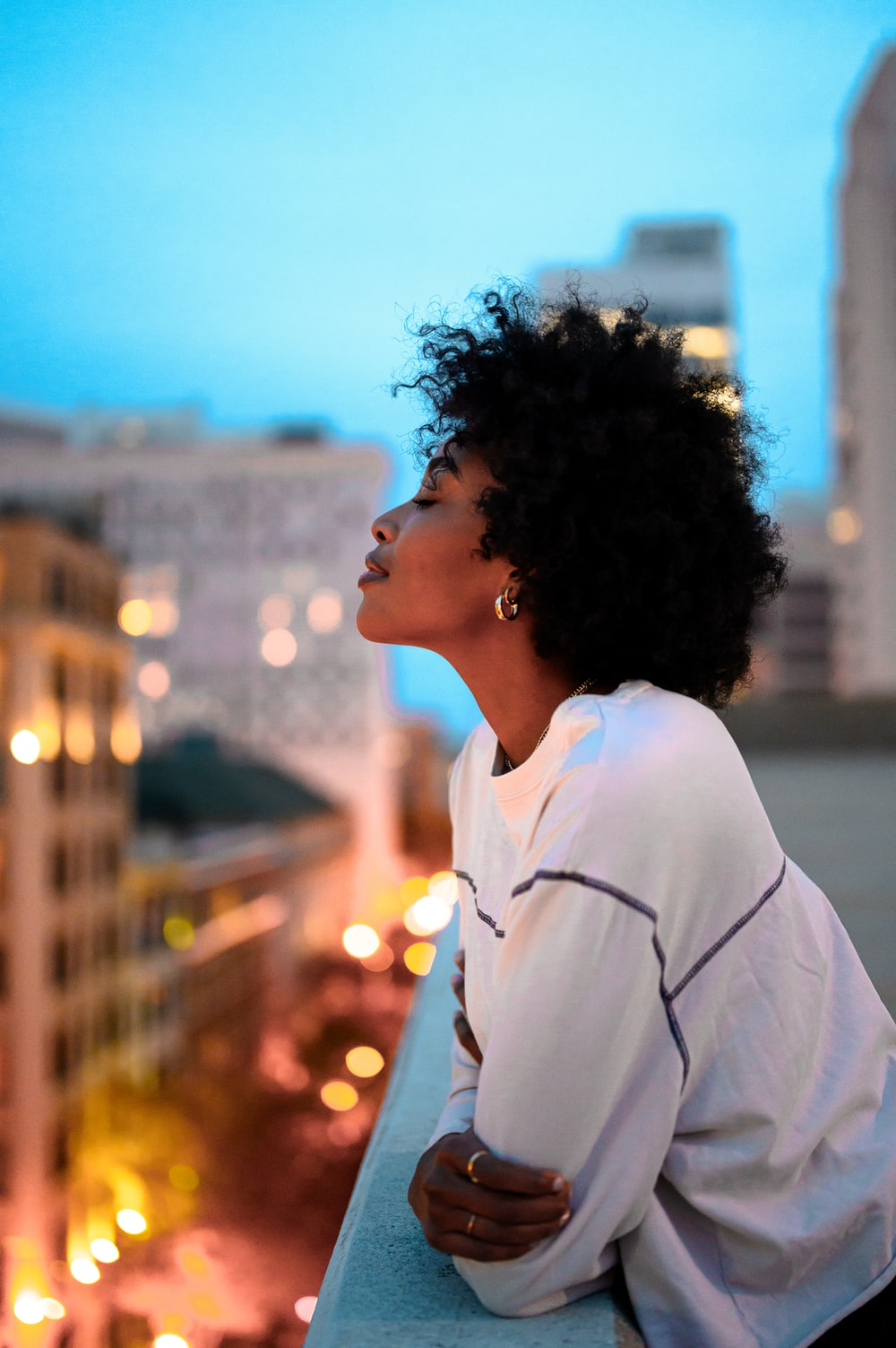 woman in white collared shirt looking at the city during night time