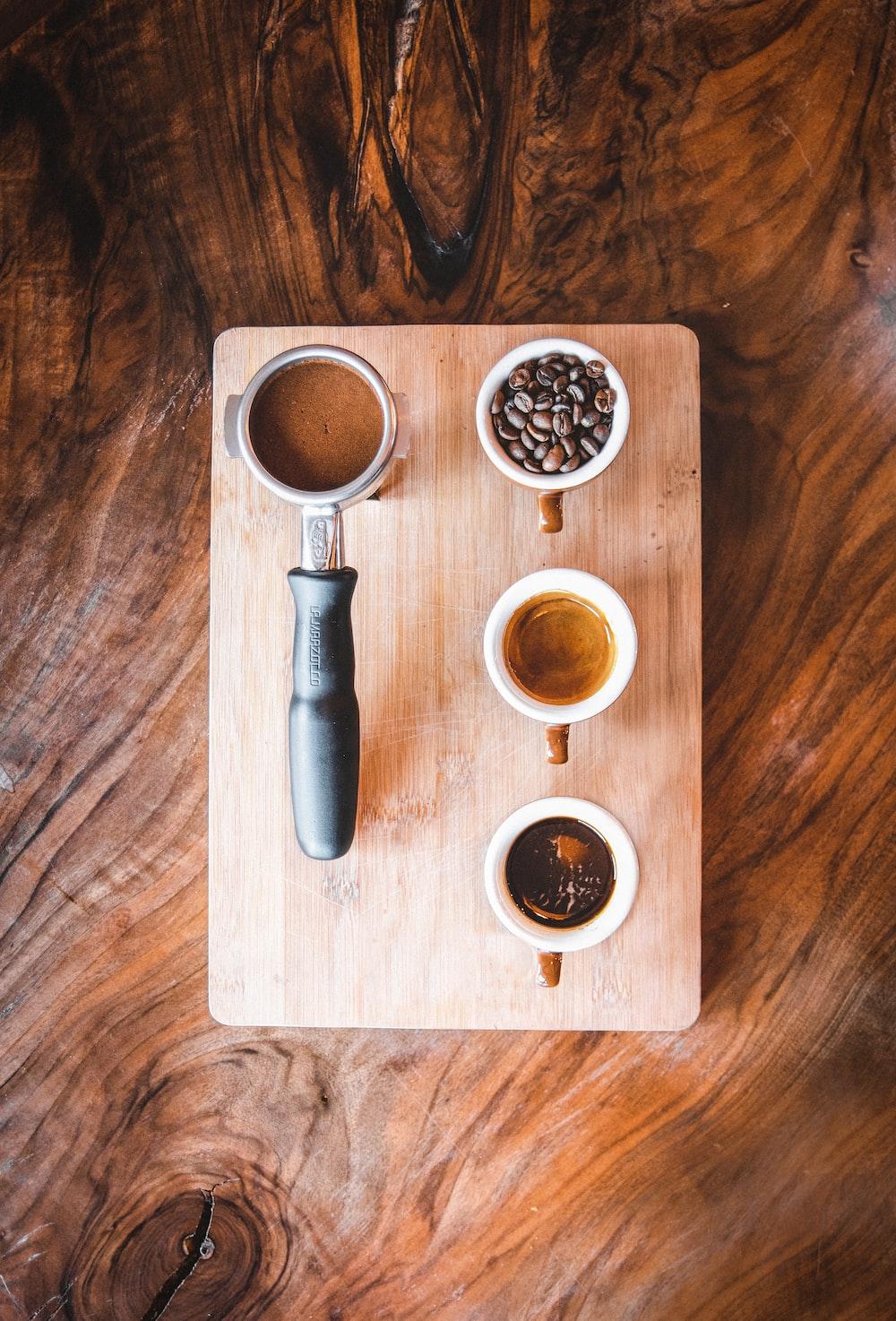 black bottle beside white ceramic mug on brown wooden table