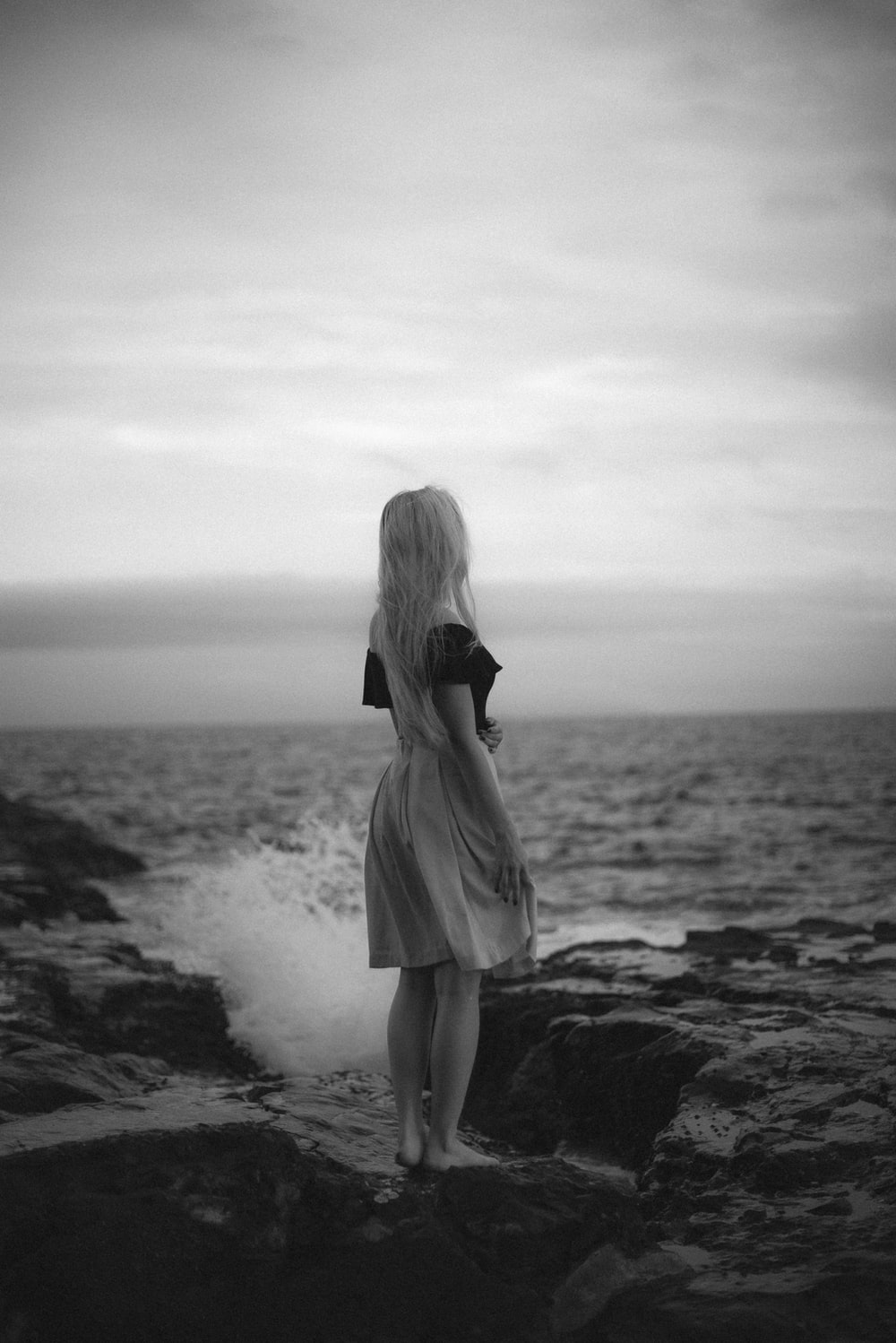grayscale photo of woman in dress standing on beach