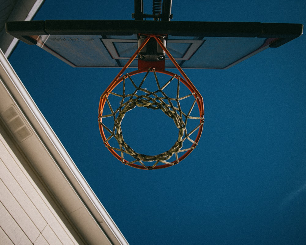 brown and white basketball hoop under blue sky during daytime