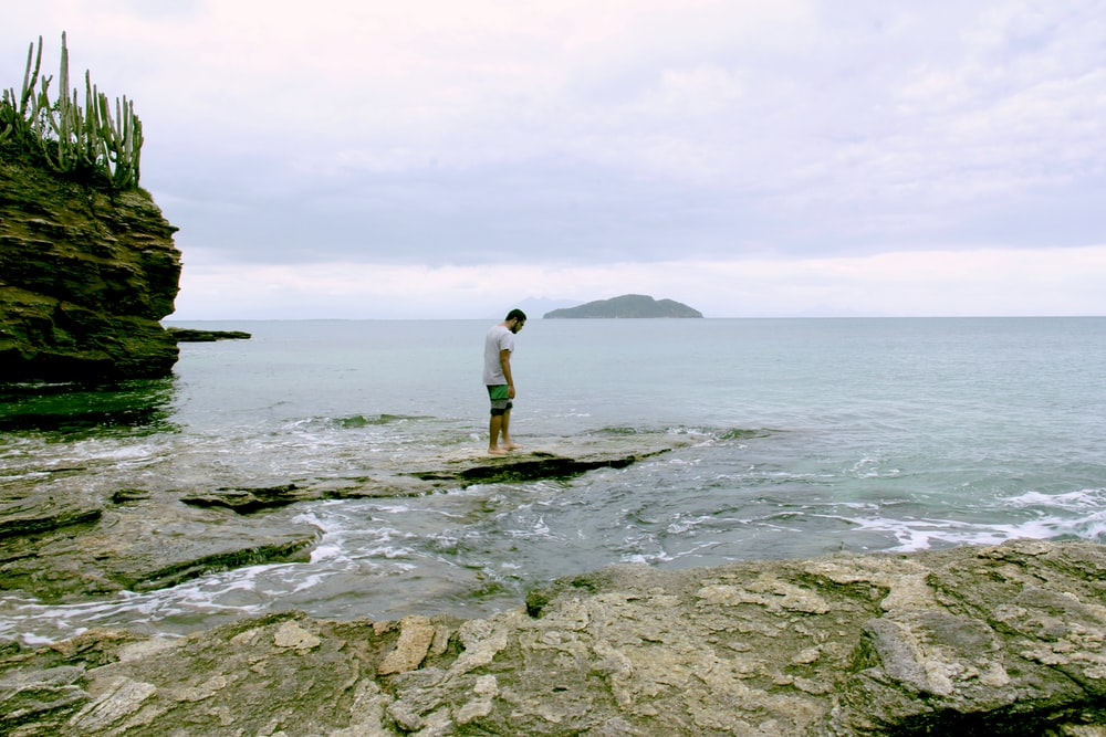 man in white shirt standing on rock by the sea during daytime