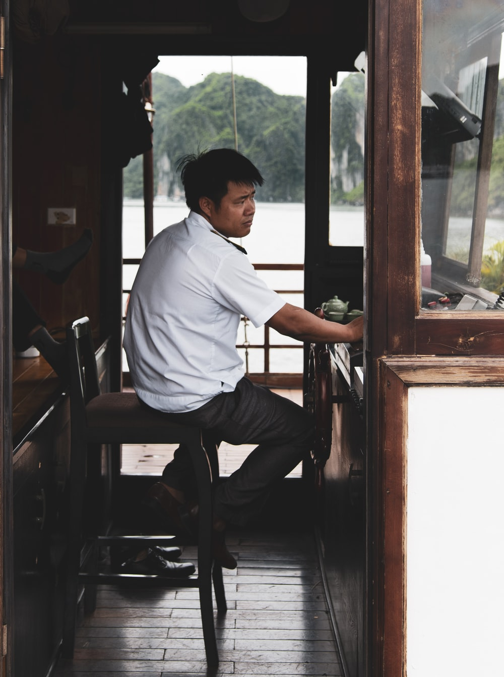 man in white dress shirt sitting on brown wooden chair