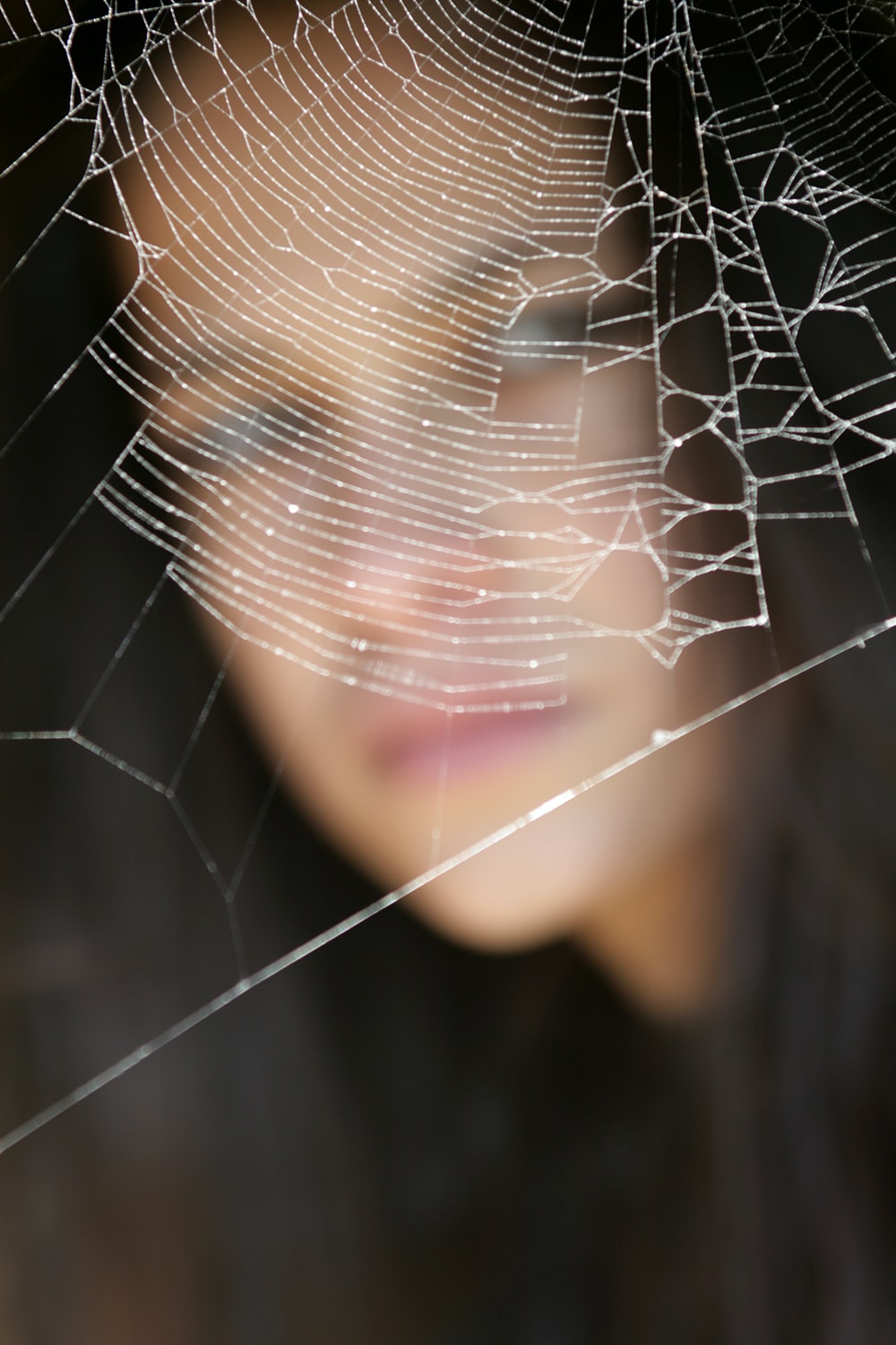 woman in black shirt with spider web on her face