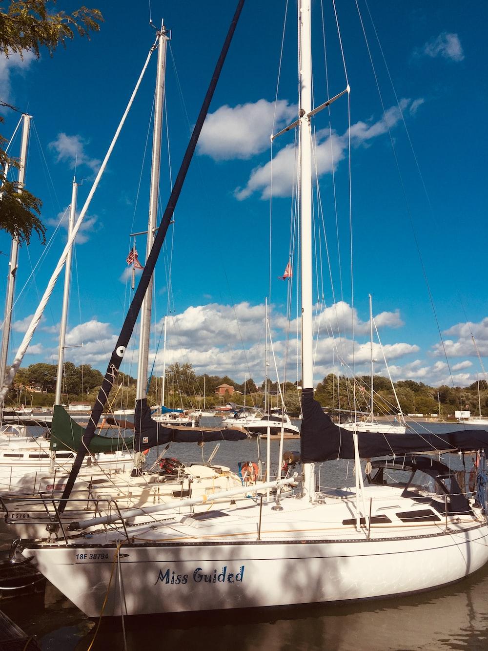 white sail boat on dock during daytime