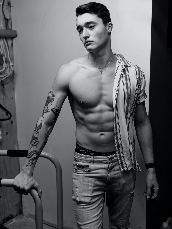 topless man in denim jeans standing near wall