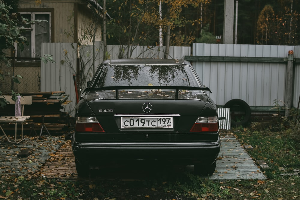 black audi a 4 parked near white wooden fence