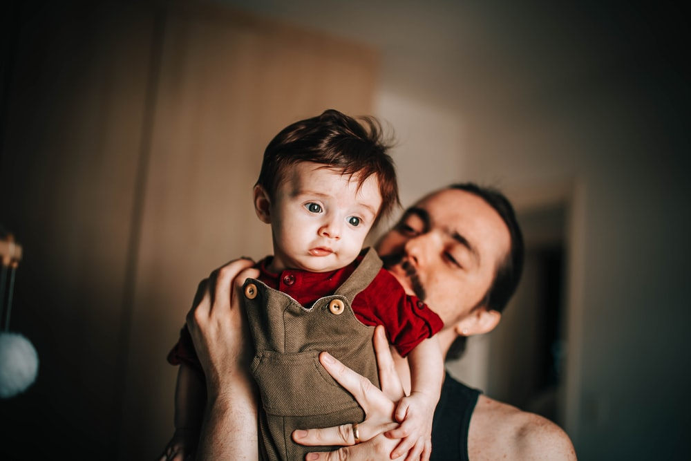 woman in black tank top carrying child in brown button up shirt