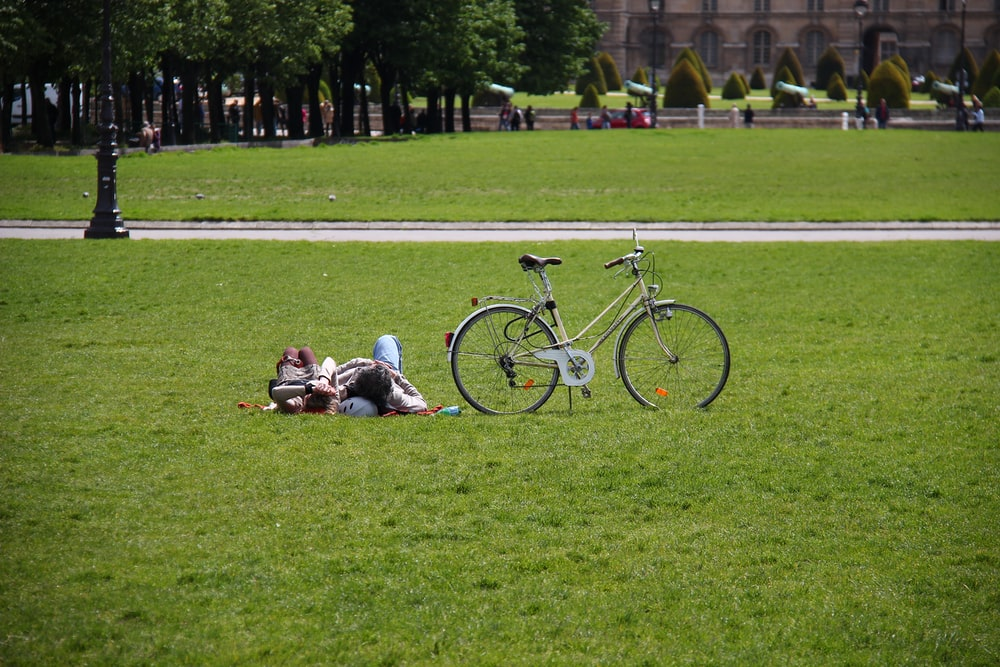 man in black shirt sitting on green grass field beside black bicycle during daytime