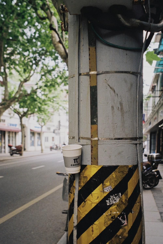 white and black trash bin beside gray concrete post