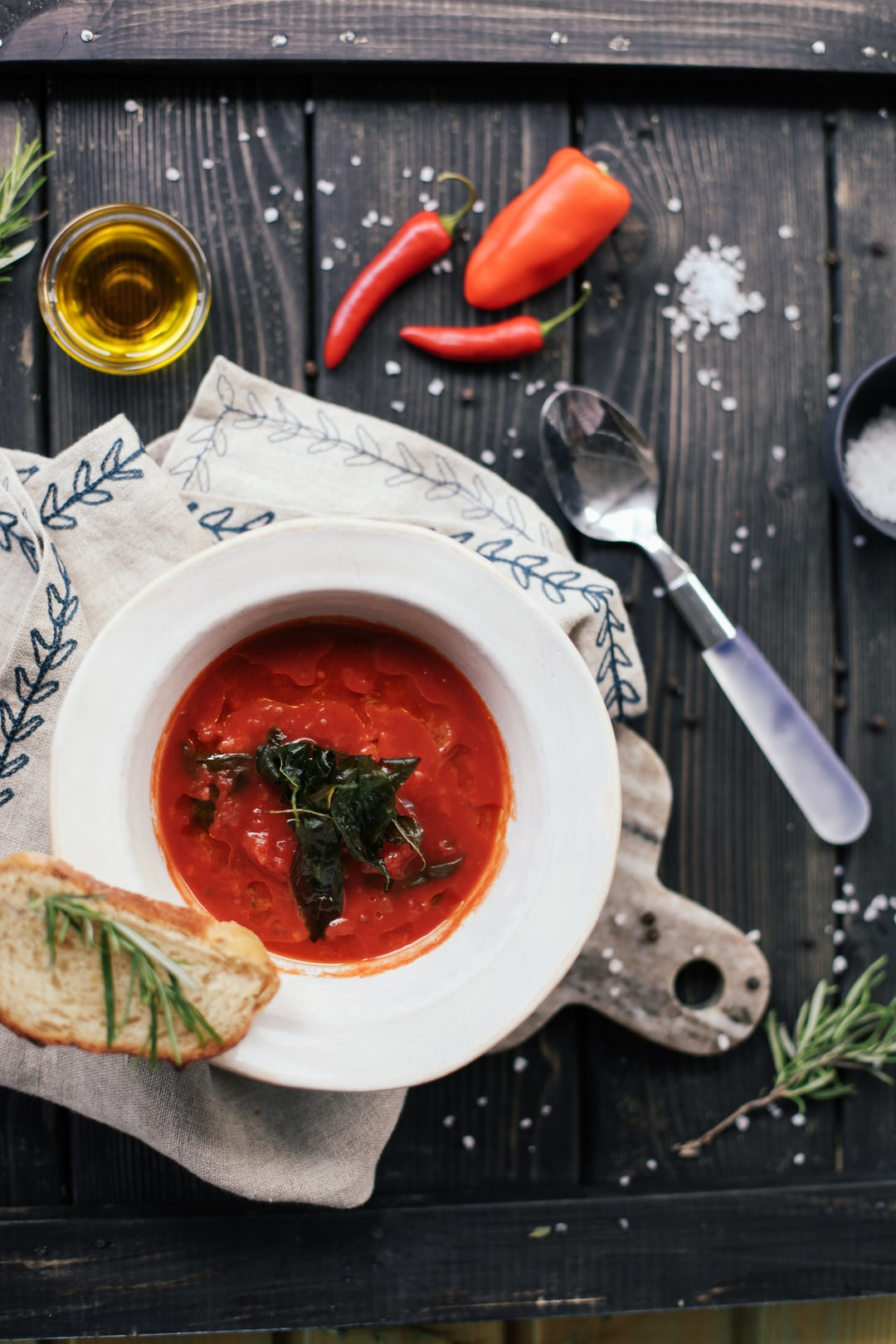 Red soup gazpacho on a wood table with herbs around, top view