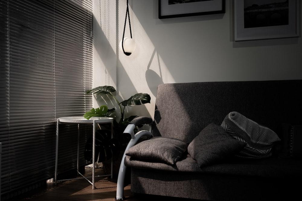gray sofa chair beside window