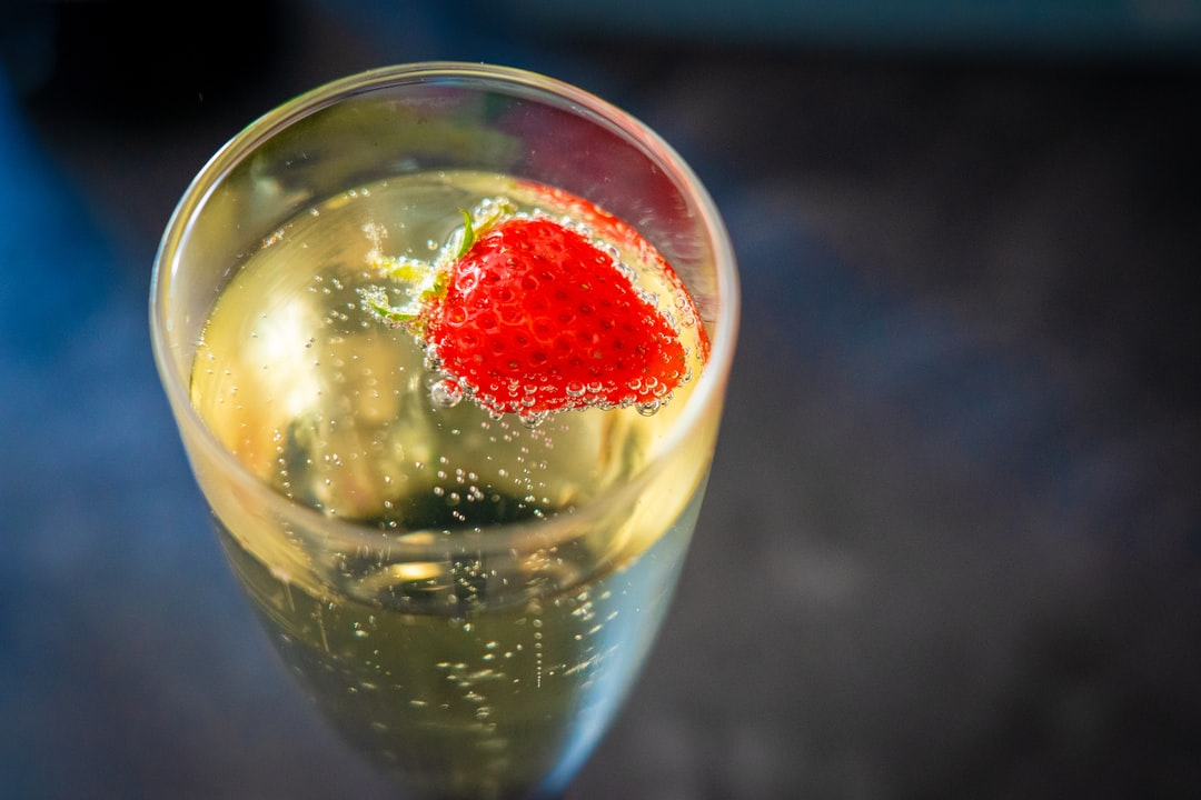 A glass of Prosecco with a strawberry.