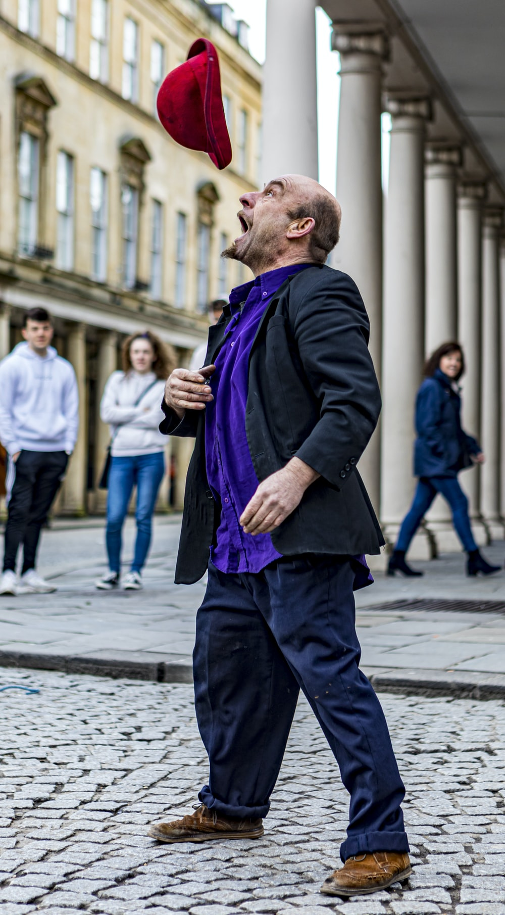 man in black suit jacket and purple scarf standing on sidewalk during daytime