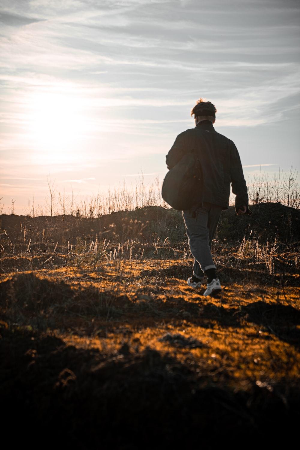 man in black jacket walking on brown grass field during daytime