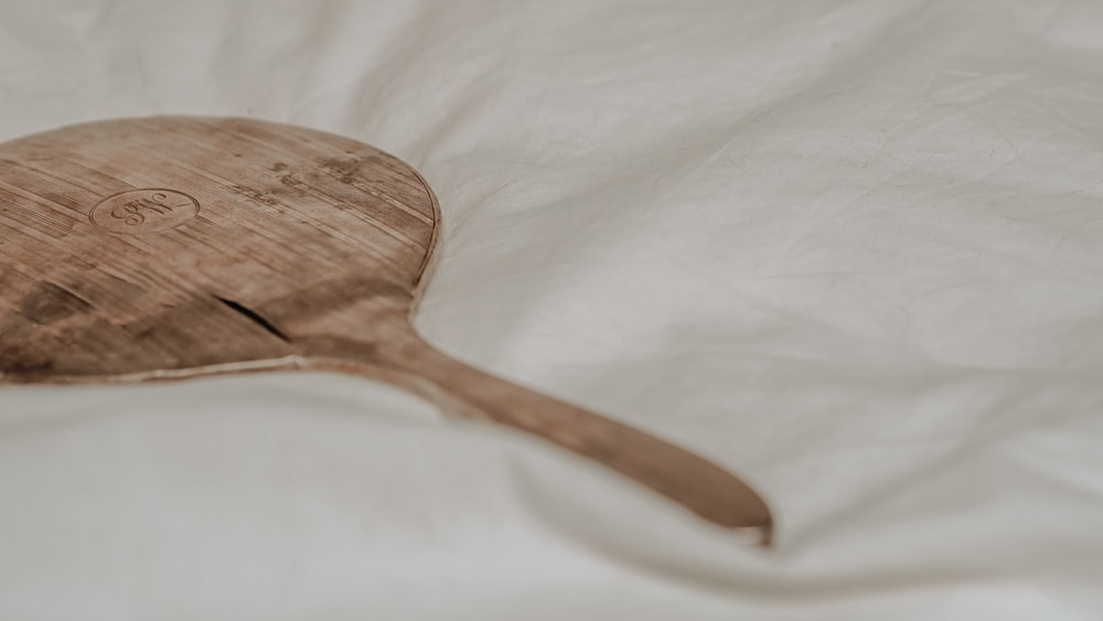 brown wooden spoon on white textile
