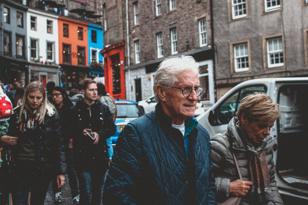 man in blue jacket standing near people walking on street during daytime