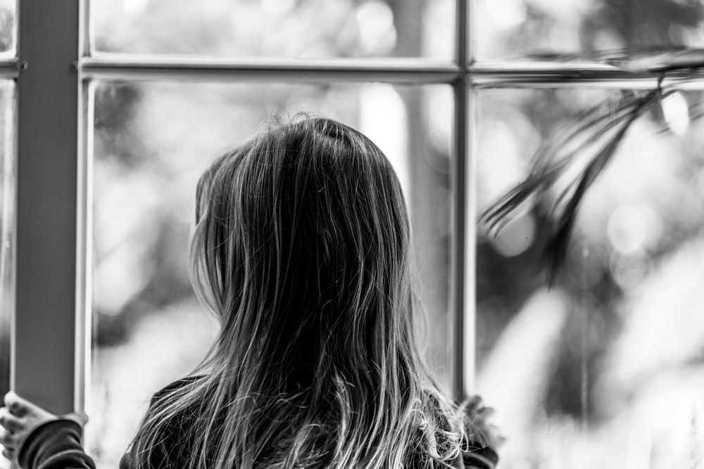grayscale photo of woman looking at the window