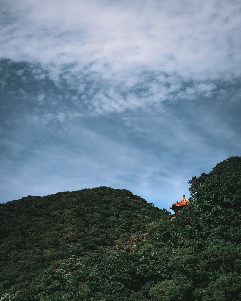 person in red jacket sitting on rock mountain under cloudy sky during daytime