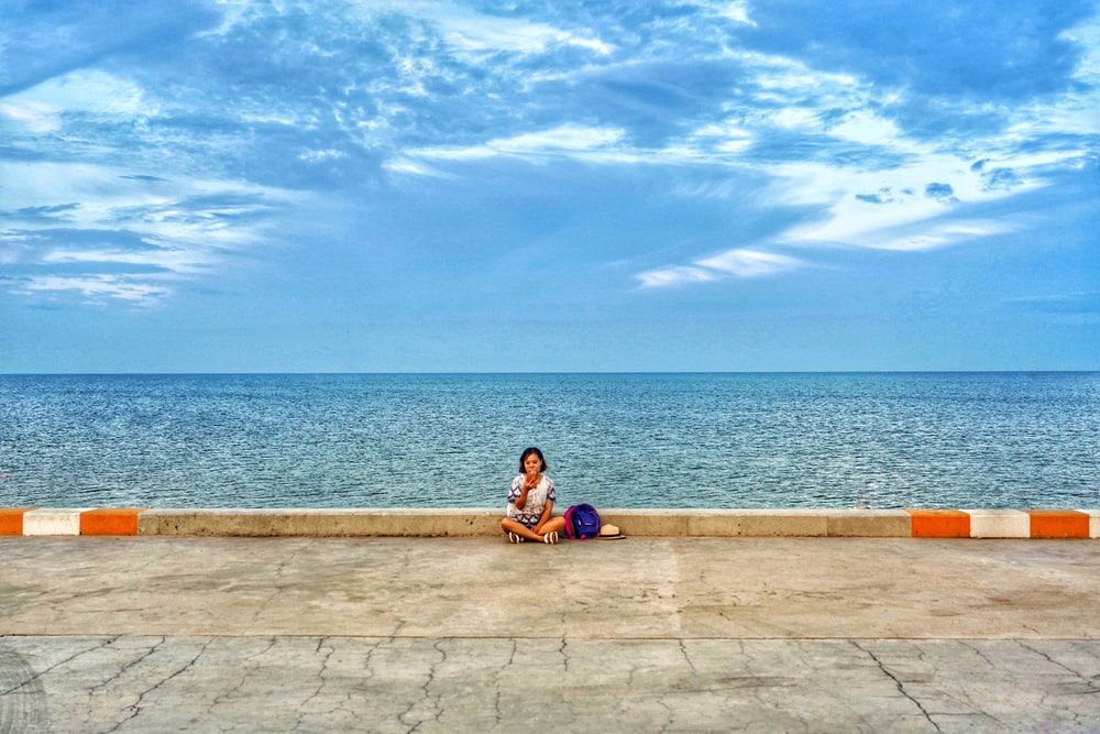 woman in blue shirt sitting on brown concrete bench near body of water during daytime