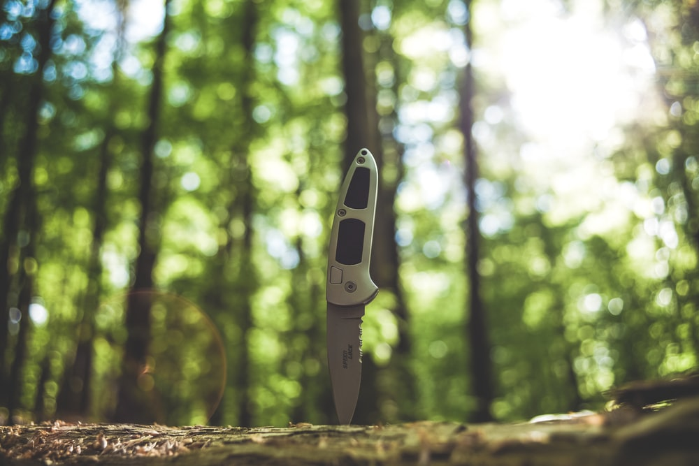 black and white knife on brown tree trunk