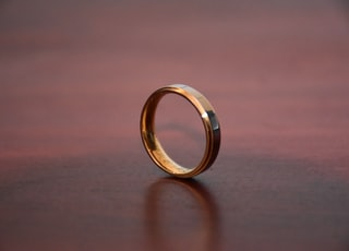gold ring on brown wooden table