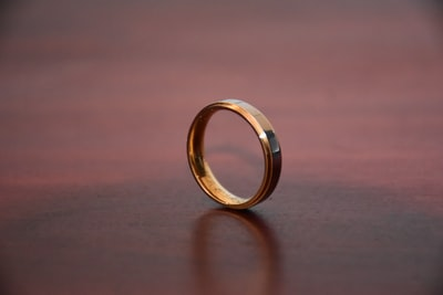 gold ring on brown wooden table ring zoom background