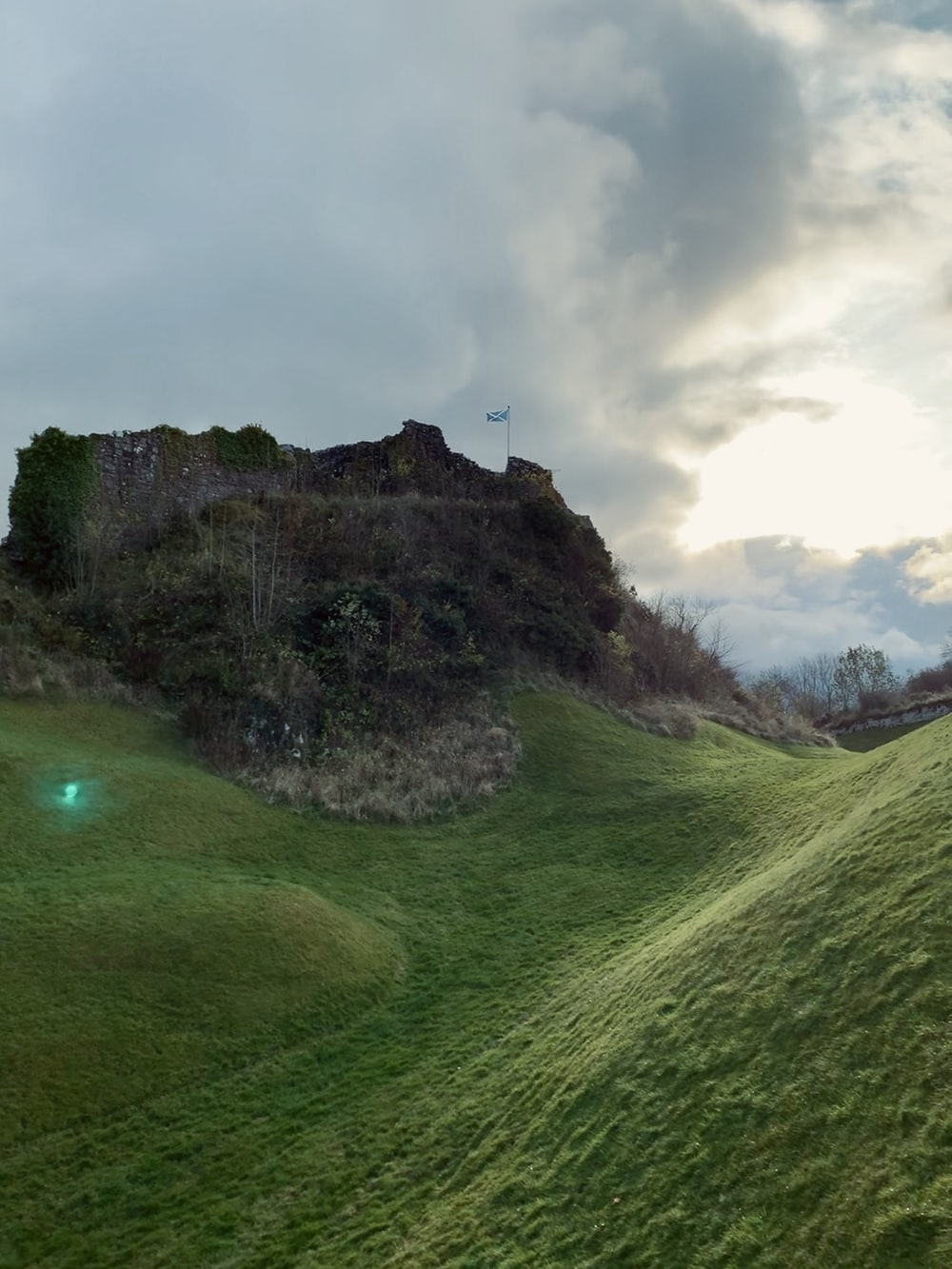 green grass field near gray rock formation under gray sky during daytime