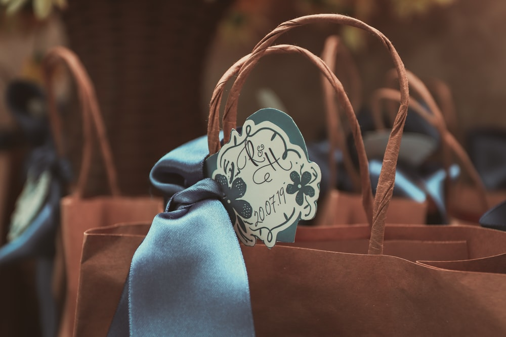 blue and white ribbon on brown leather tote bag