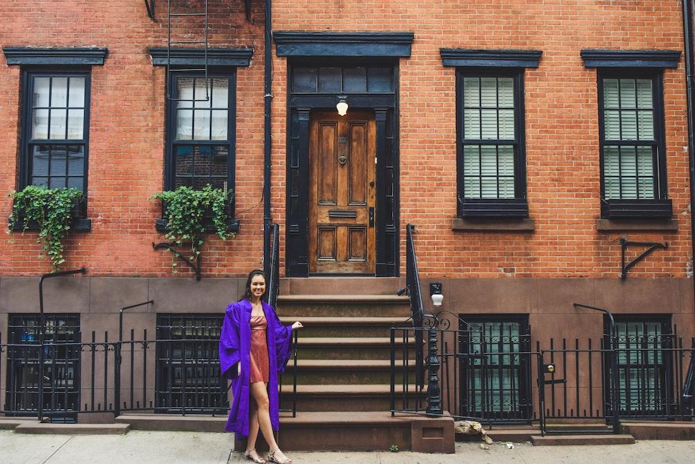 woman in purple long sleeve shirt and black pants standing near brown wooden door