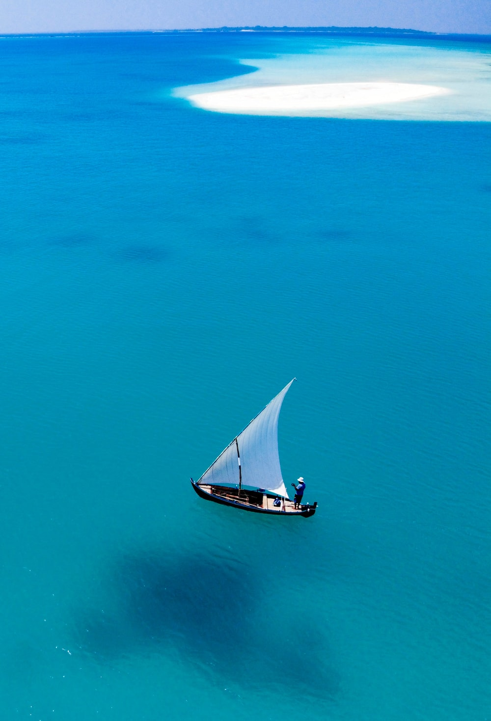 white and black sailboat on blue sea