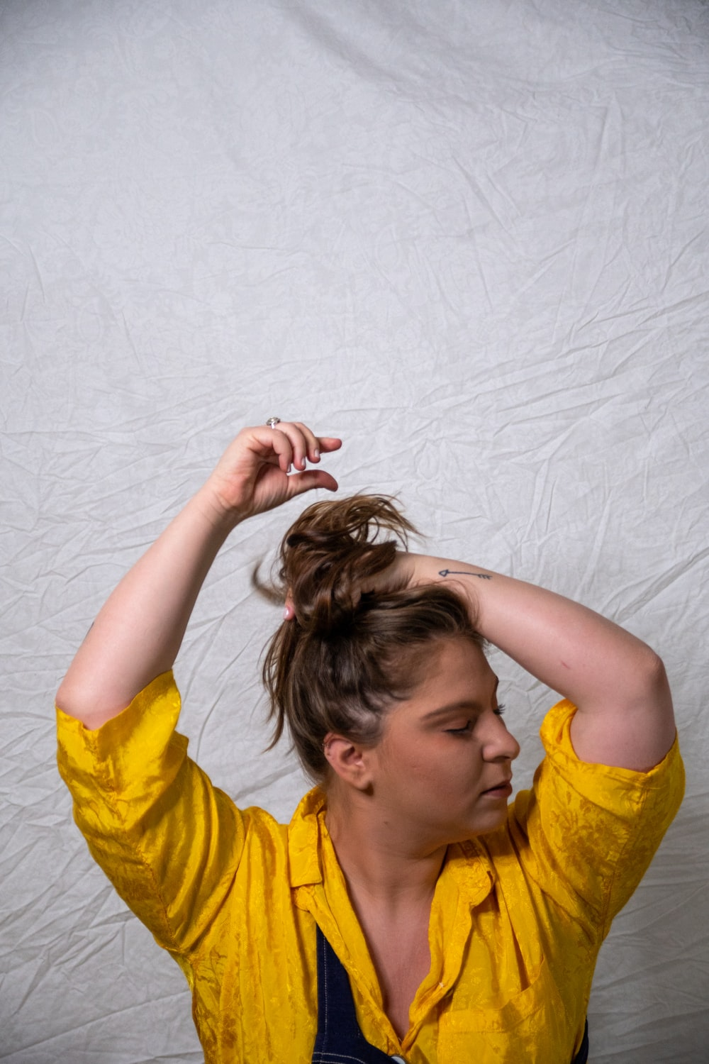 woman in yellow crew neck t-shirt holding her hair