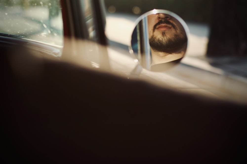 man in black sunglasses looking at the car window during daytime