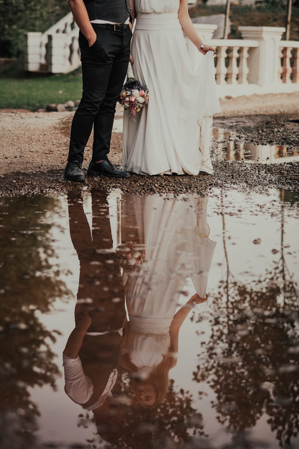 woman in white wedding dress holding hands with man in black suit